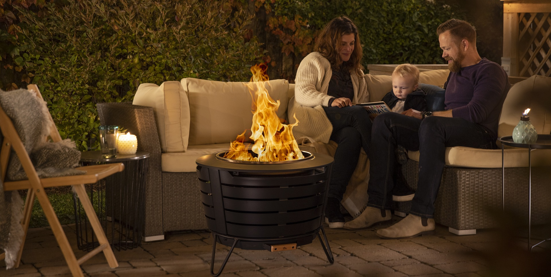 family reading book near fire pit