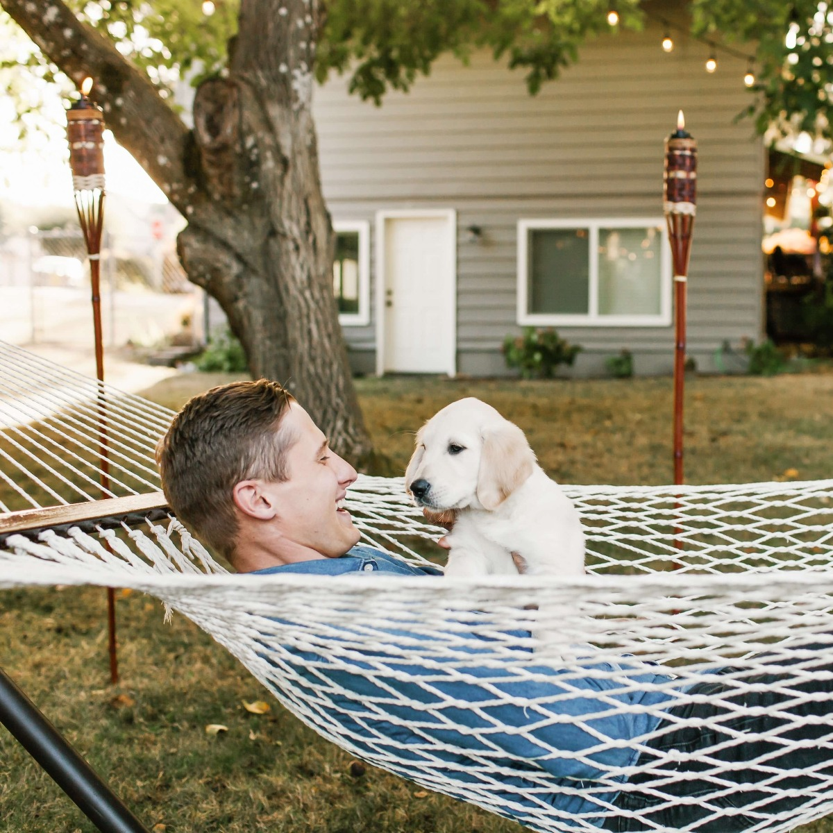 man with puppy in hammock with tiki torches