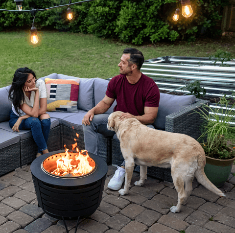 couple around fire pit with dog